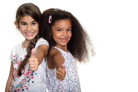 Cute hispanic and african-american small girls doing the thumb up sign and smiling - Isolated on white