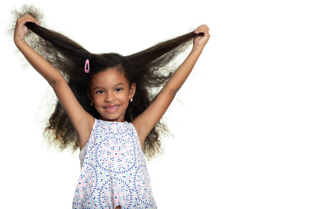 Cute african american small girl playing with her long curly hair - Isolated on white