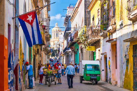 cubaStreet scene with cuban flag on a colorful street in Old Havana with a view of the Presidential Palace Редакционное