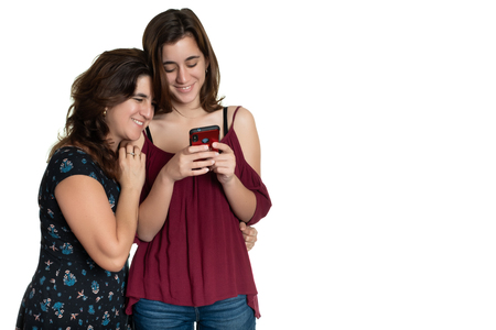 Hispanic teenage girl and her affectionate mother looking at a smartphone and smiling - Isolated on white Фото со стока