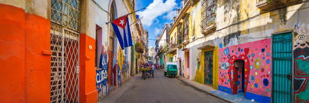 Panoramic urban scene with a cuban flag on a colorful street in Old Havana