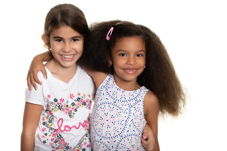 Hispanic and african american small girls hugging - Isolated on white