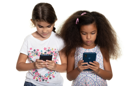 Two small girls using their smartphones - Isolated on white