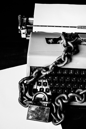 Information censorship concept - Typewriter locked with a chain and padlock - In black and white Фото со стока