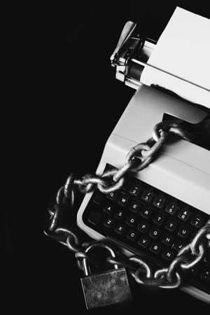 Concetto di censura delle informazioni - Macchina da scrivere bloccata con una catena e un lucchetto - In bianco e nero isolato su sfondo nero black