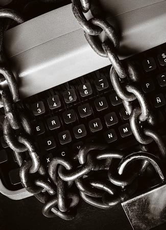 Concept de censure de l'information - Machine à écrire verrouillée avec une chaîne et un cadenas sur fond noir