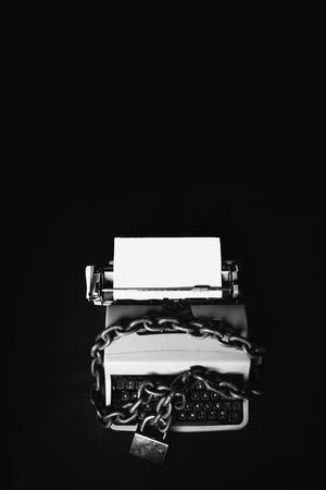 Concetto di censura delle informazioni - Macchina da scrivere bloccata con una catena e un lucchetto su sfondo nero