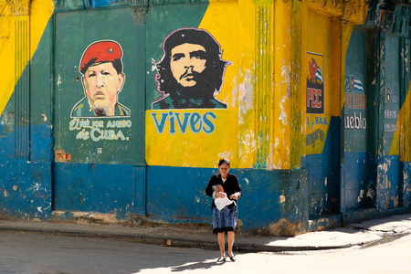 Old woman walks next to a wall in Havana painted with the faces of Che Guevara and Hugo Chavez