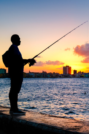 Silhouette of a man fishing on the bay of Havana at sunset with a view of the city skyline Фото со стока