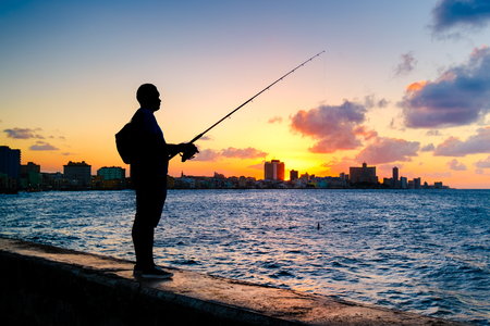 Silhouette of a man fishing on the bay of Havana at sunset with a view of the city skyline Stock Photo