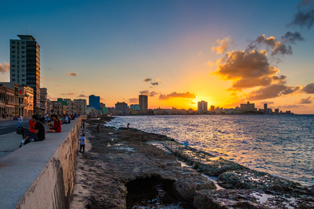 HAVANA,CUBA - FEBRUARY 9,2019 : People sitting on the malecon seawall in Havana during a beautiful sunset with a view of the city skyline