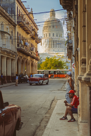Urban scene with people and old cars in Havana with the Capitol on the background Editorial