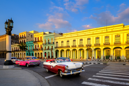Classic cars and colorful buildings in downtown Havana at sunset