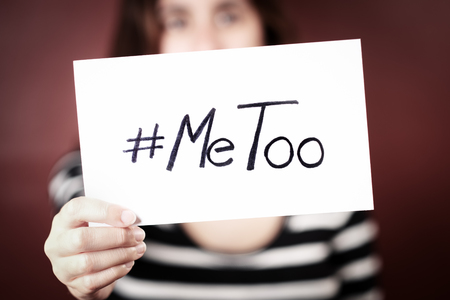 Young adult woman holding a sign with the hashtag MeToo - her face is out of focus