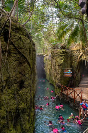 XCARET,MEXICO - APRIL 16,2019 : Visitors enjoying the underground river at the XCaret park on the Mayan Riviera