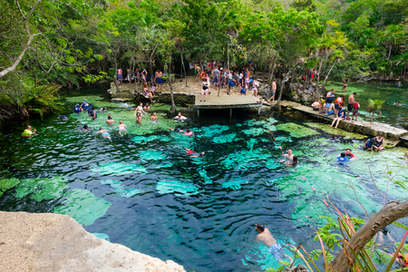 QUINTANA ROO, MEXICO - APRIL 15,2019 : Locals and tourists enjoying an open air cenote at the Yucatan jungle in Mexico