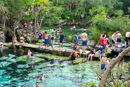 QUINTANA ROO, MEXICO - APRIL 15,2019 : Locals and tourists enjoying an open air cenote at the Yucatan jungle in Mexico Фото со стока - 122152886
