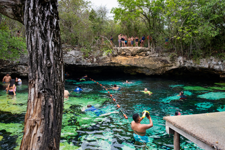 QUINTANA ROO, MEXICO - APRIL 15,2019 : Locals and tourists enjoying an open air cenote at the Yucatan jungle in Mexico Banque d'images - 122152888