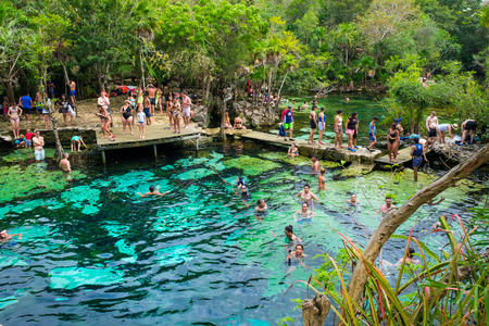 QUINTANA ROO, MEXICO - APRIL 15,2019 : Locals and tourists enjoying an open air cenote at the Yucatan jungle in Mexico Фото со стока - 122152889