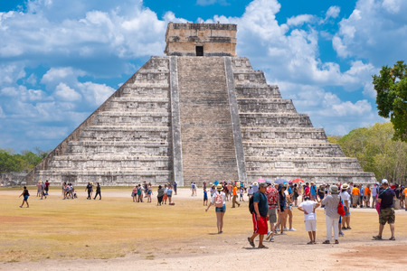 Tourists next to the Pyramid of Kukulkan on a beautiful day at the ancient mayan city of Chichen Itza Редакционное