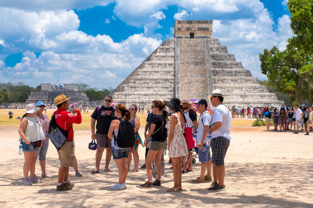 Tourists hear an explanation from their guide next to the Pyramid of Kukulkan at Chichen Itza Banque d'images - 123342141