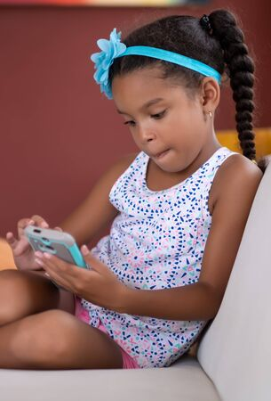 Small african american girl using a mobile phone at home Banque d'images