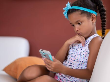 Small african american girl using a mobile phone at home