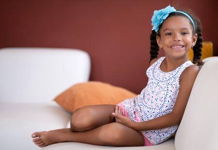 Jolie fille afro-américaine assise sur un canapé et souriant Banque d'images