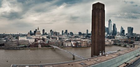 Panoramic view of London on a cloudy day with St Paul Cathedral, The Millennium Bridge, The Tate Gallery and the City
