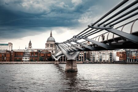 Saint Paul Cathedral and the Millennium Bridge in London on a typical cloudy day