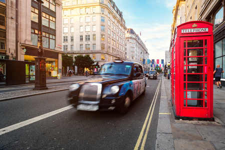 Black cab and red phone booth at The Strand, one of the most famous avenues in London Redakční