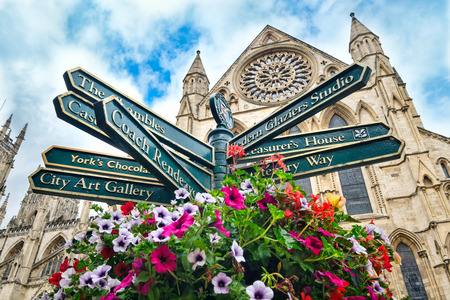 Street sign with directions to landmarks in the english city of York - With the York Cathedral on the background