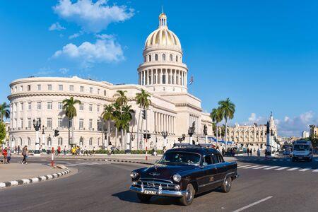 Escena callejera con viejos coches clásicos y el famoso Capitolio de La Habana.