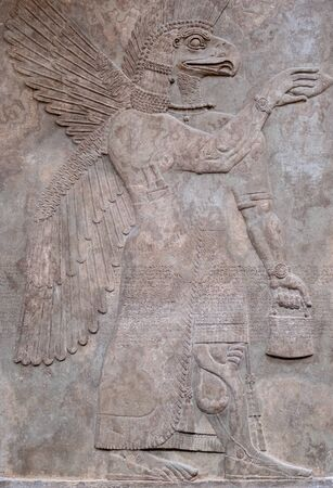 Detail of an ancient persian bas-relief depicting a winged god with the head of an eagle