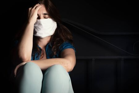 Sad and stressed sick young woman wearing a face mask to avoid spreading an infectious disease