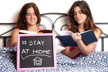 Mother and daughter in a bedroom reading a book during a quarantine with a Stay At Home sign - Selective focus, focused on the sign