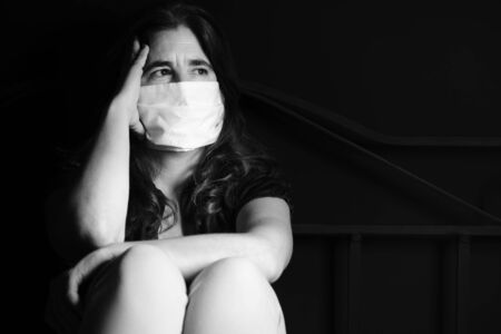 Stressed and sad woman wearing a face mask to avoid respratory diseases - Black and white portrait sitting on a bed Standard-Bild