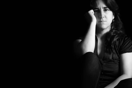 Sad and lonely woman with a thoughtful expression - Black and white portrait on a black background with copyspace Standard-Bild