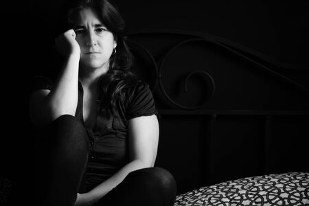 Sad and lonely woman with a thoughtful expression - Black and white portrait sitting on her bed Standard-Bild