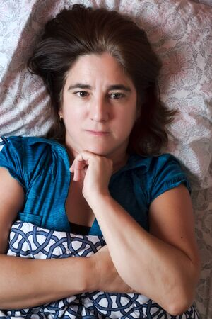 Woman laying in bed with a worried and sad expression - Sickness, Stress, Depression, Anxiety