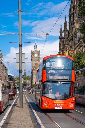 Red double decker bus at Princes Street in Edinburgh on a sunny summer day