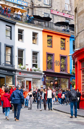 Colorful shopfronts and tourists at the famous Victoria Street in Edinburgh Editorial