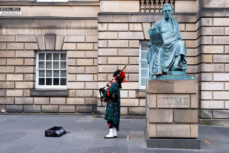 Bagpipe player in traditional Scottish kilts next to the David Hume statue in Edinburgh