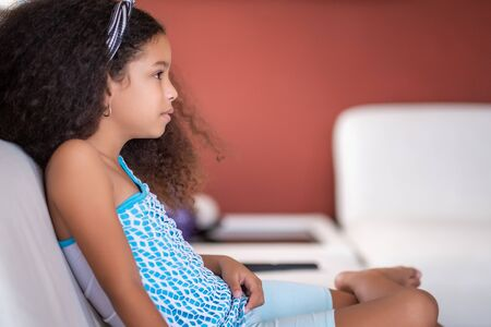 Cute multiracial small girl with beautiful curly hair watching TV at home Фото со стока