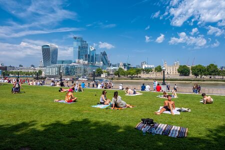 People enjoying summer near Tower Bridge in London with a view of the City skyline Archivio Fotografico