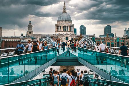 The Millennium Bridge and St Paul Cathedral in London on a typical cloudy day Фото со стока