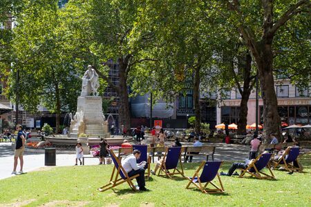 People enjoying summer at Leicester Square in central London Фото со стока