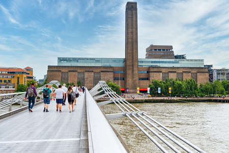 The Millennium Bridge and the Tate Modern museum in London Редакционное