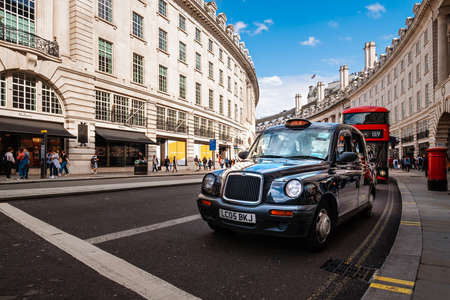 Typical London black cab at Regent Street, a famous landmark of the british capital Редакционное