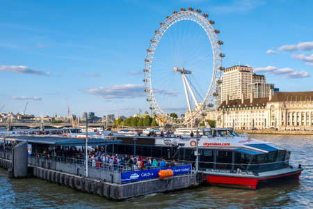 Thames river boats terminal at Westminster Bridge with a view of the Southbank and the London Eye